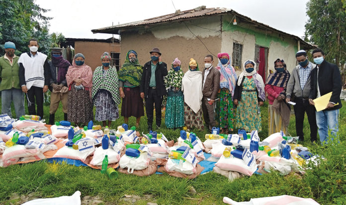 Israeli aid packages are delivered to Ethiopians in Debre Berhan; 100 more were delivered in Kechene, outside Addis Ababa. Lovers of Zion Association leaders Michael Moges (white tallit katan) and Belayneh Tazebku (brown jacket) helped with the distribution.