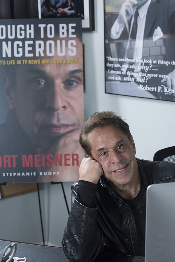 Mort Meisner with a poster of his book cover in the background.