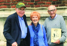 Sen. Carl Levin, Winnie Krieger and Aaron Krieger at the entrance of their old school holding one of their old Durfee yearbooks