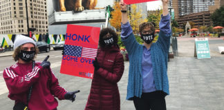"Leah Berman, Jenna Friedman and Tania Miller held up signs that said ""Honk if you're registered"" and gave away masks at Campus Martius in Detroit."