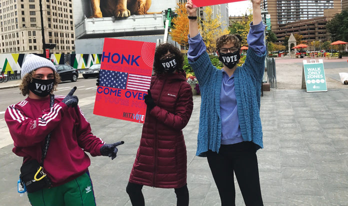"""Leah Berman,Jenna Friedman and Tania Miller heldup signs that said""""Honk if you're registered"""" and gaveaway masks at Campus Martius in Detroit."""