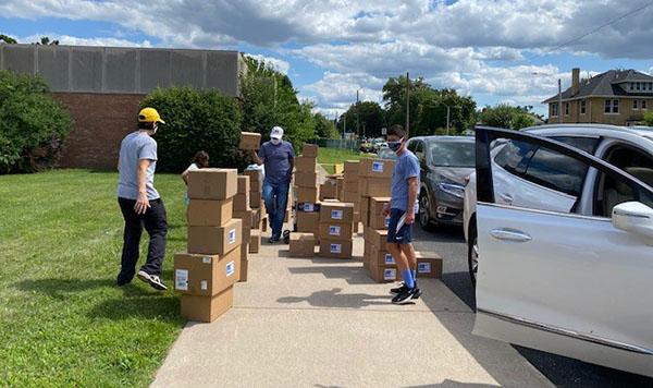 Teen volunteers work to distribute the boxes to those in need.