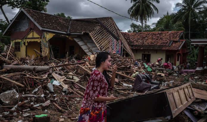 A woman looks at the destruction of her home in the tsunami that ravaged the Indonesian island of Sumatra, Dec. 22, 2018