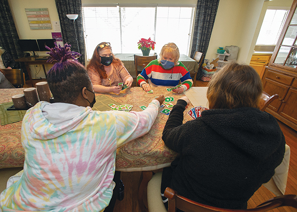 Shannon Brandt of Farmington Hills and Executive Director Karen Moore play cards with Katrise and Jesa