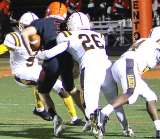 North Farmington's Noah Rioux (26) makes a tackle during the Raiders' state playoff win over Fenton.