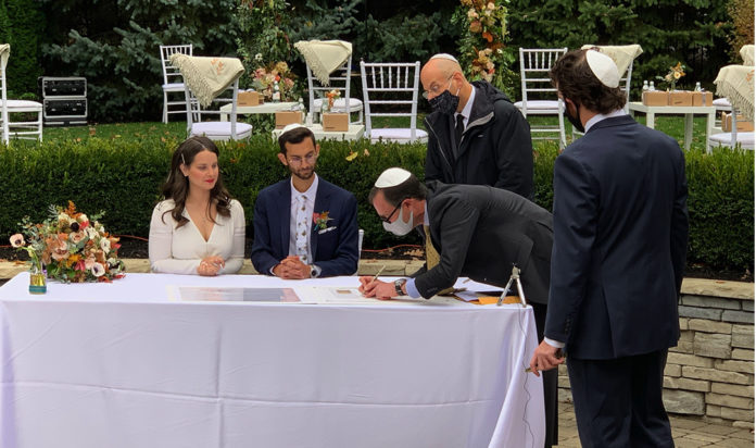 Signing of the ketubah: Laura Williams, Jacob Allen, Rabbi Aaron Bergman (standing), Lee Trepeck (signing) and Jon Shaw (back to camera).