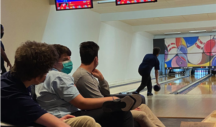 Frankel Jewish Academy bowlers Andy Tukel, left, Aiden Schafer and Gabe Gordon watch teammate Eli Gordon bowl Feb. 24 during a match against Detroit Loyola at Langan's All Star Lanes in Walled Lake.