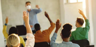 Back view of group of students raising their arms during a class at lecture hall. stock photo