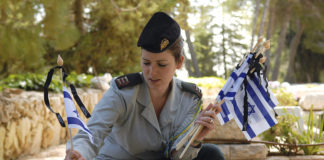 An IDF officer places new flags, each with a black ribbon, on the graves of IDF soldiers for Yom HaZikaron.