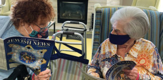 Meer residents Esther Liwazer and Rita Sills enjoy their free copies of the Jewish News.