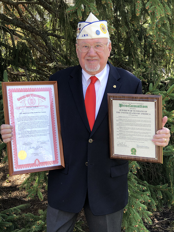 Dr. Ed Hirsch, Commander of the Jewish War Veterans, Department of Michigan proudly displays proclamations honoring the JWV on their 125th anniversary.