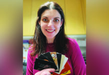 JSL Senior Life Director Leslie Katz holding donated restaurant gift cards for Project Take-Out.