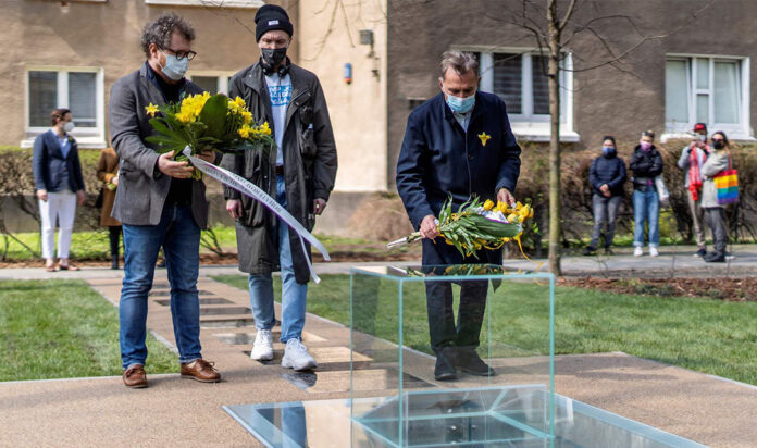 Participants lay a wreath and flowers in front of a monument dedicated to the underground archives of the Jewish ghetto during its unveiling ceremony at the site in Warsaw, April 19, 2021.