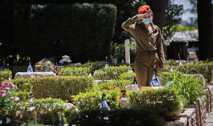 An Israeli soldier places flowers on the graves of fallen Israeli soldiers at the Mount Herzl military cemetery hours before the start of Memorial Day, April 20, 2020.