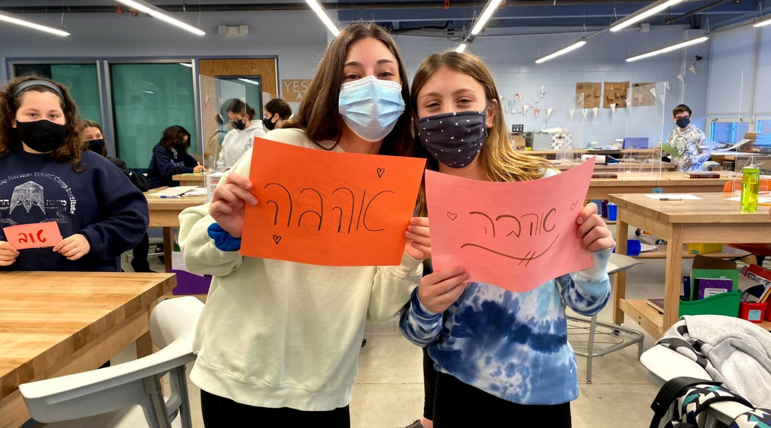 Jewish day school students, like these at the Solomon Schechter Day School of Bergen County bearing signs with the Hebrew word for love, are increasingly pushing their schools to explore how they can foster greater diversity, equity and inclusion both in school and out in the world.