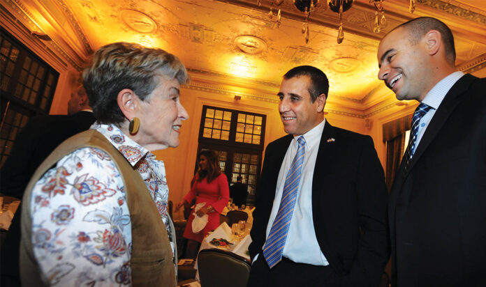 Consul General Aviv Ezra and David Kurzmann of the JCRC speak to a woman at an event.
