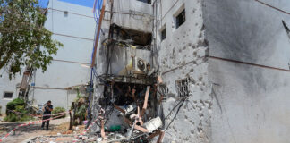 People seen at their home that was hit yesterday by a rocket fired from the Gaza Strip, in the southern Israeli city of Ashdod, on May 18, 2021.
