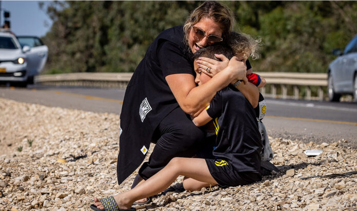 A woman and child take cover as a siren sounds a warning of incoming rockets fired from the Gaza strip on a road between Ashkelon and Sderot, southern Israel, on May 19, 2021.