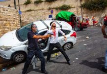 An Israeli policeman fends off an angry mob, after they swarmed an Israeli motorist, pelting his car with stones and driving him off the road, outside Jerusalem's Old City, May 10, 2021.