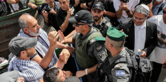Israeli security forces clash with protesters during a protest against Israel's plan to evict Palestinians from the eastern Jerusalem neighborhood of Sheikh Jarrah on May 10, 2021. Itamar Ben-Gvir, a far-right Israeli lawmaker, is at right wearing a white kippah.