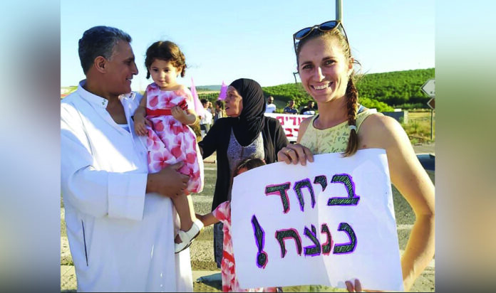 """Tamar Shooval attends a peace rally in the Partnership 2Gether region with her Arab neighbors and daughter. The sign reads """"Together Forever."""""""