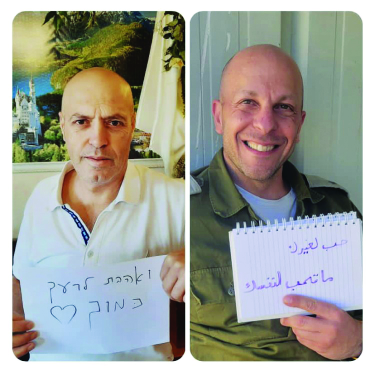 """Two Partnership 2Gether volunteers, Heshem Bsharat from Yaffa and Nitsan Moran from Jezreel Valley, holding signs in each other's language saying """"love thy neighbor as thyself."""""""