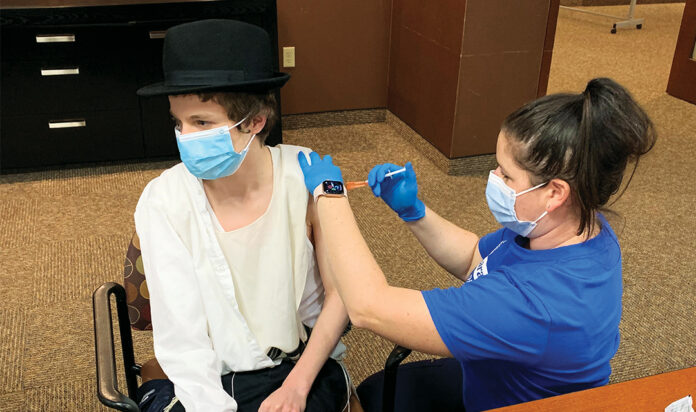 A student from Chabad's boys school receives the first dose of the vaccine.