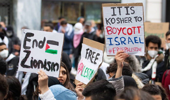 Demonstrators against Israel hold signs at a rally in Vienna, Austria, where protesters chanted in Arabic about a massacre of Jews, May 13, 2021.