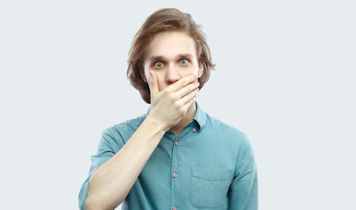 Portrait of shocked handsome long haired blonde young man in blue casual shirt standing, covering his mouth and looking at camera with big eyes