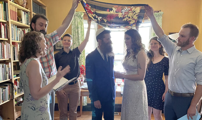 The happy couple celebrate under the chuppah in front of a few family members and friends.
