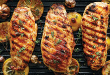 Grilled chicken breasts with thyme, garlic and lemon slices on a grill pan close up