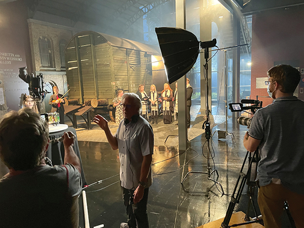 Documentary director Keith Famie engineers the filming of the unveiling of Hailey Callahan's train car artwork at the Holocaust Memorial Center.