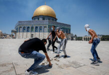 Palestinian worshippers gather rocks to throw at the Al-Aqsa mosque compound in Jerusalem's Old City, June 18, 2021.