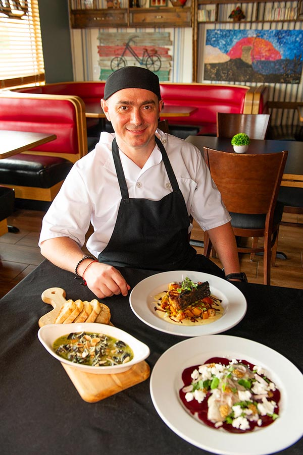 Chef Yakov Fleysher at one of his tables with some dishes.