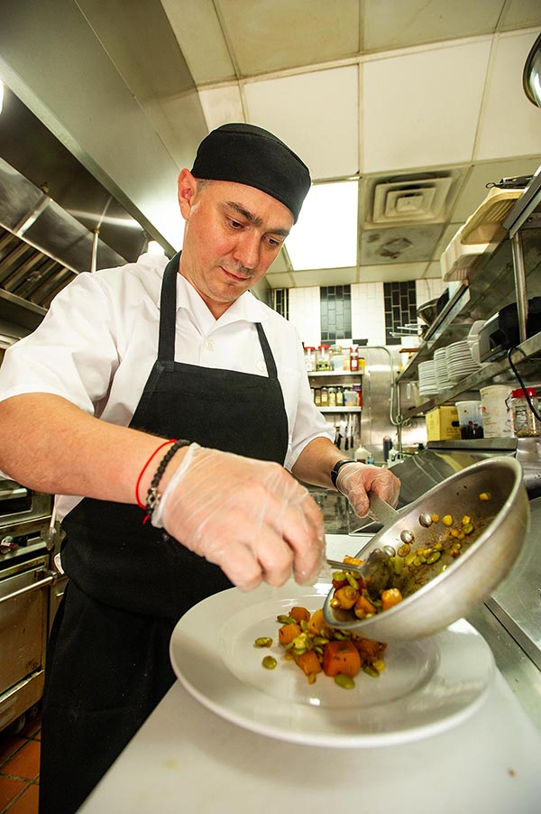 Chef plates the vegetables.