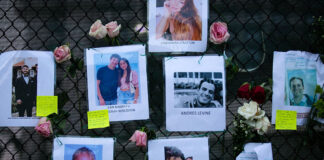 Images of Andres Levine, Ilan Naibryf and Deborah Berezdivin, three of the Jewish victims of the Surfside building collapse, in center among other photographs of those missing posted at a makeshift memorial on the building site in Surfside, Fla., June 26, 2021.