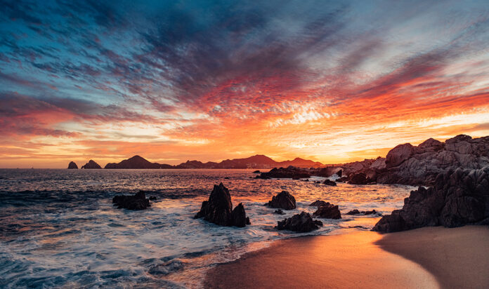 Dramatic sunset in Cabo San Lucas with the view of Lands End at the horizon, Mexico.