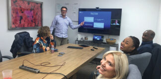 Guests gather to watch a live event in the Birmingham headquarters of M3Linked, clockwise from left, Carolyn Koblin, Steven Nelick, Roy Sadler, Franka Sadler and Stacy Latona.