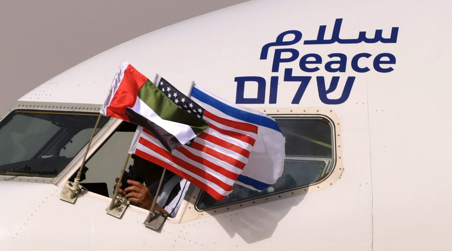 """An El Al plane flying the flags of Israel, the United Arab Emirates and the United States, and bearing the word """"peace"""" in Arabic, English and Hebrew, arrives at the Abu Dhabi airport from Tel Aviv, Aug. 31, 2020."""
