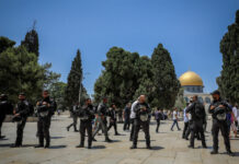 Israeli security forces guard as a group of religious Jews visit the Temple Mount, also known as Haram al Sharif, in Jerusalem's Old City, during Tisha b'Av, July 18, 2021.