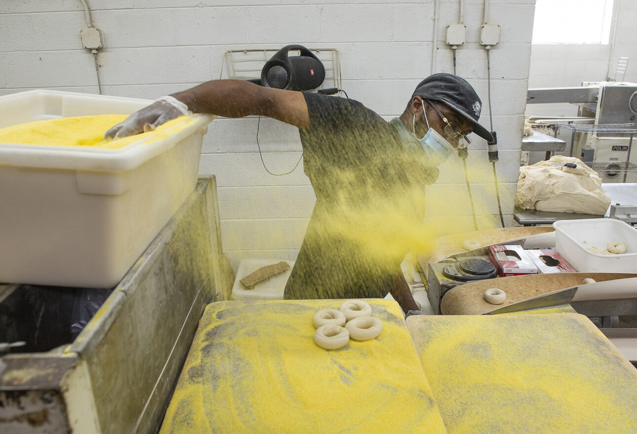 Timothy McNeal of Detroit throws cornmeal onto the bagel trays.