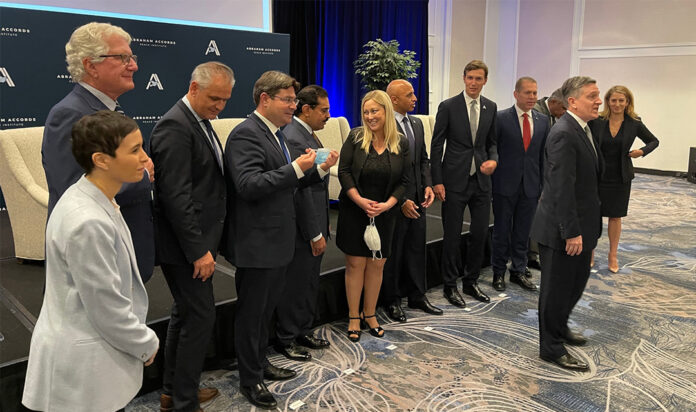 Jared Kushner, fourth from right, poses for a group photo with the ambassadors from Israel and the UAE and others at the Four Seasons Hotel in Washington, Sept. 14, 2021.