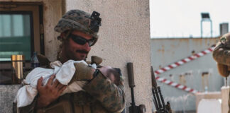 Sgt. Matt Jaffe, a U.S. Marine assigned to the 24th Marine Expeditionary Unit (MEU) holds a baby during an evacuation at Hamid Karzai International Airport, Kabul, Afghanistan, in this photo taken on Aug. 20, 2021.