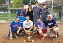 Kosher Ribs celebrates its Inter-Congregational Men's Club fall softball league championship. Mitch Kline couldn't play in the playoffs, but Evan Kline made sure his father was in the Kosher Ribs team photo, holding a cellphone showing Mitch Kline on a FaceTime call.