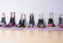 """Participants practice the """"Leg Up Wall"""" pose."""